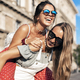 Young female giving piggyback ride to friend - PhotoDune Item for Sale