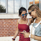 Young female tourists using smartphone during walk - PhotoDune Item for Sale