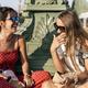 Cheerful women sitting on bridge and using cellphone - PhotoDune Item for Sale