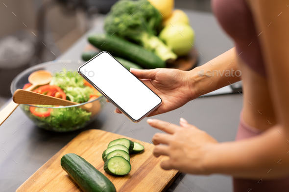 Woman Using Smartphone Cooking Healthy Dinner For Weight-Loss In Kitchen - Stock Photo - Images