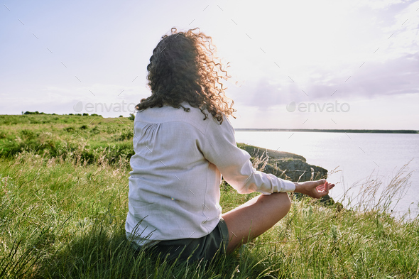 Meditating by tranquil lake - Stock Photo - Images
