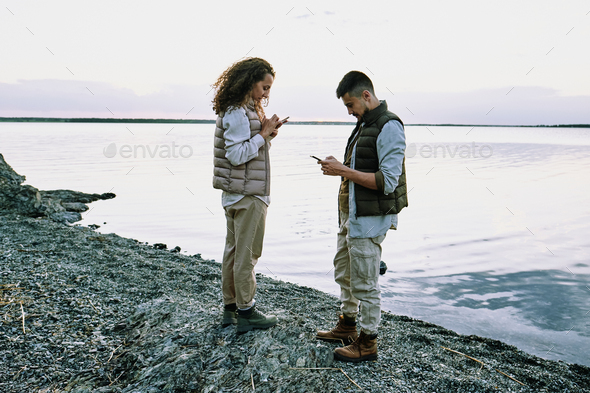 Couple using gadgets at lake - Stock Photo - Images