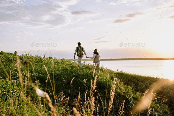Holding hand of girlfriend while hiking hills - Stock Photo - Images