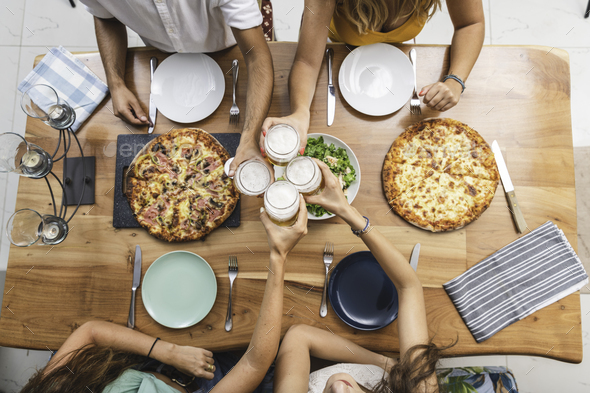 Top View of Friends Cheering With Beers and Having Pizzas - Stock Photo - Images