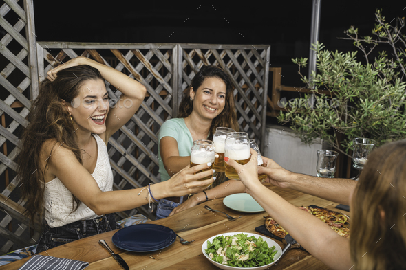 Beautiful Friends Laughing and Cheering With Beers and Eating Pizza - Stock Photo - Images