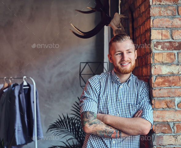Portrait of a bearded modern male with tattoos on his arms. - Stock Photo - Images