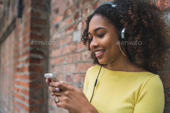 Afro-American woman with mobile phone and headphones - Stock Photo - Images