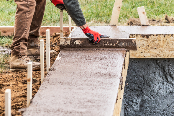 Construction Worker Leveling Wet Cement Into Wood Framing - Stock Photo - Images