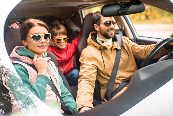 Happy friendly family travelling by car on rural road