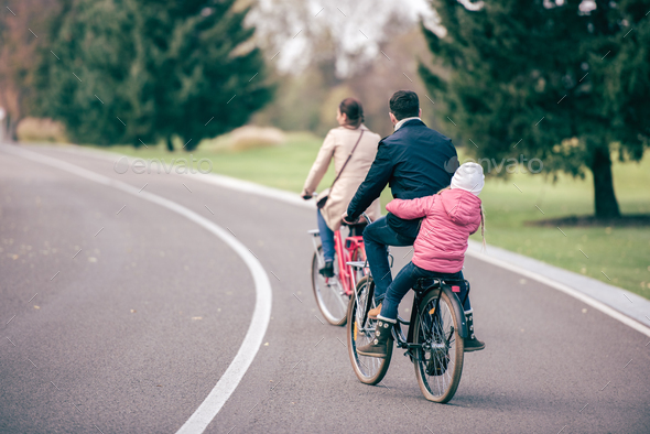 Back view of young family riding bicycles in autumn park, father carrying his daughter on bike
