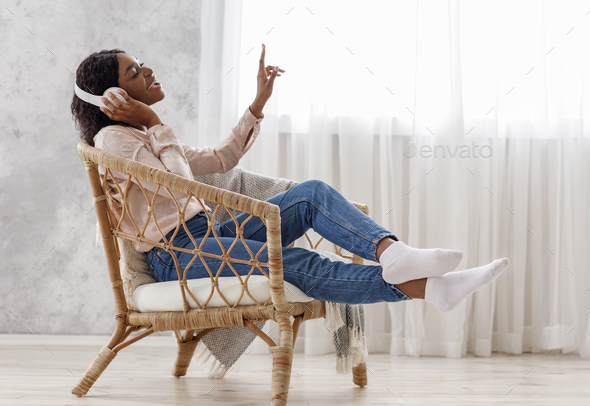 Joyful African Woman Singing While Listening Music With Wireless Headphones At Home - Stock Photo - Images