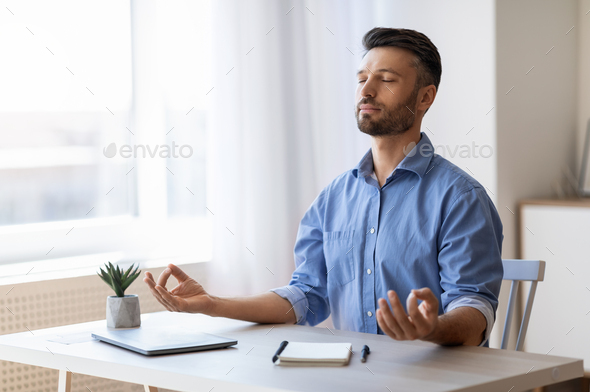 Calm Millennial Businessman Meditating At Workplace, Practicing Zen Yoga At Work, Coping With Deadline Stress In Office, Relaxing At Desk With Eyes Closed, Doing Breathing Exercises, Free Space