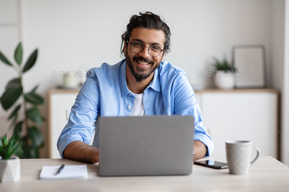 Happy Indian Freelancer Man Sitting At Desk With Laptop, Smiling At Camera - Stock Photo - Images