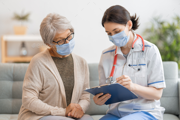 Doctor and senior woman wearing facemasks - Stock Photo - Images