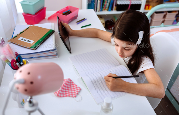 Girl studying at home with tablet and mask on table - Stock Photo - Images