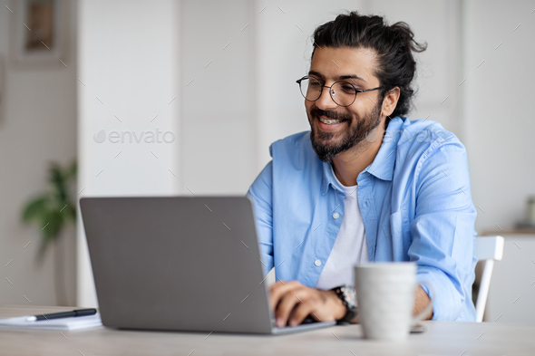 Smiling Indian Writer Using Laptop Computer, Sitting At Desk In Home Office  Stock Photo by Prostock-studio
