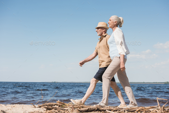 Side view of happy senior couple holding hands and walking on sandy beach - Stock Photo - Images