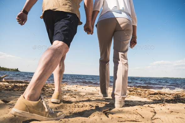 Cropped shot of senior couple holding hands and walking on sandy beach - Stock Photo - Images