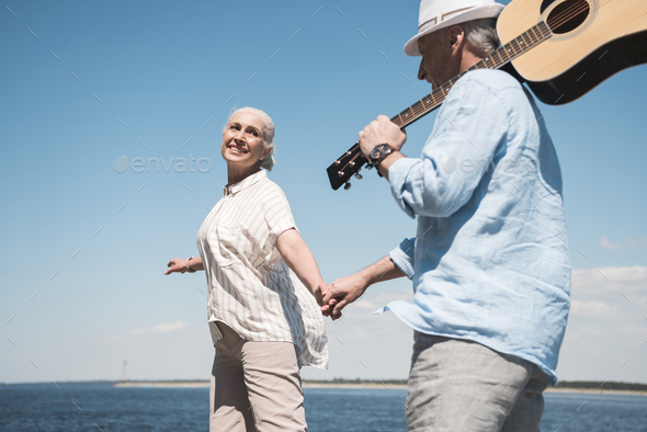Happy senior couple with guitar holding hands and walking at quay - Stock Photo - Images
