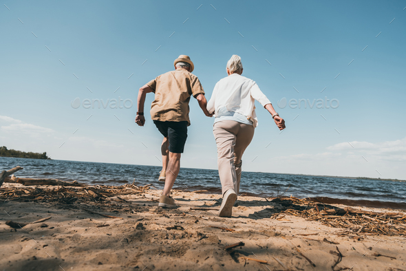 Back view of senior couple holding hands and running on sandy beach - Stock Photo - Images