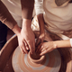 Male Teacher Helping Woman Sitting At Wheel In Pottery Class - PhotoDune Item for Sale