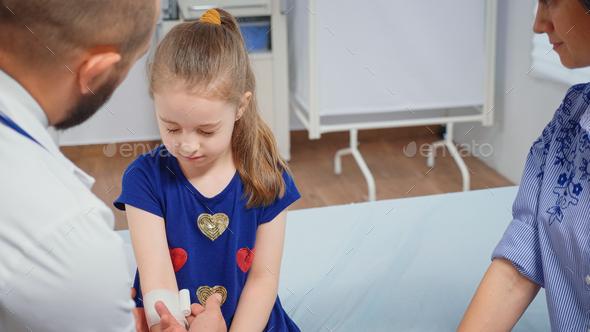 Doctor bandaging child hand - Stock Photo - Images