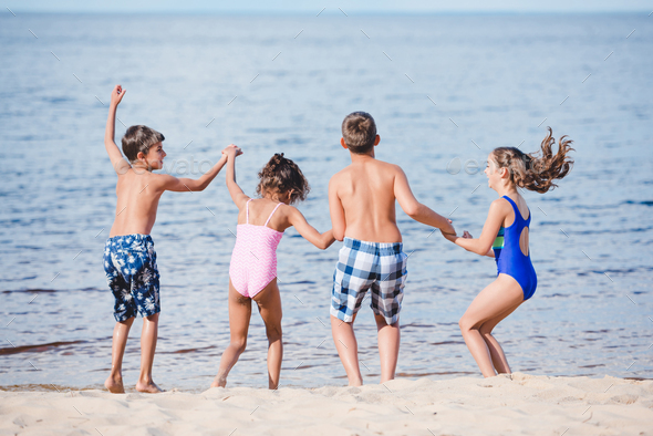 rear view of group of little children holding hands while standing on sandy beach - Stock Photo - Images