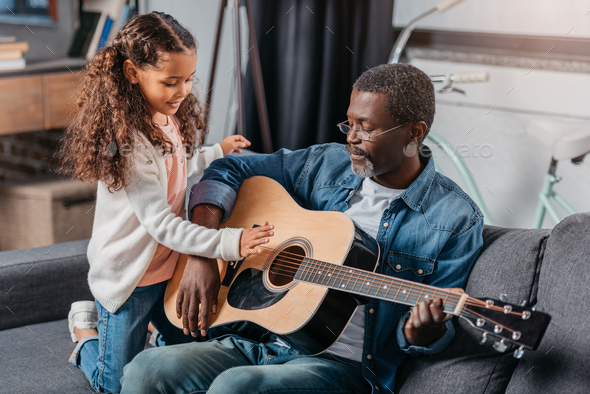 African american man playing guitar with his cute daughter - Stock Photo - Images