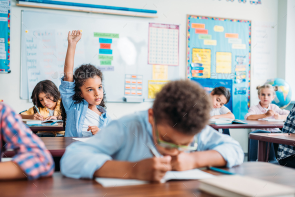 african american girl raising hand in class - Stock Photo - Images