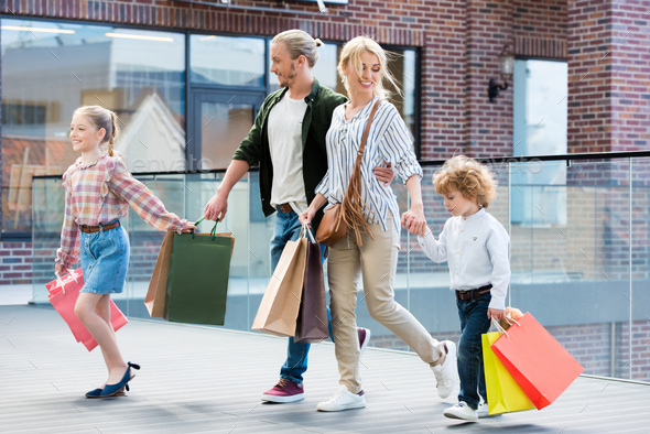 parents and little kids walking with shopping bags in mall - Stock Photo - Images