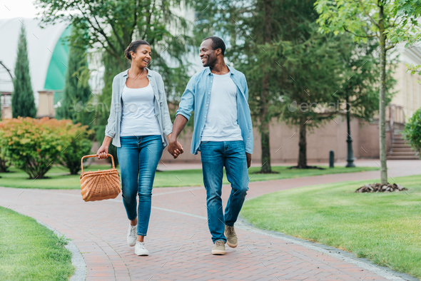 african american couple with picnic basket holding hands while walking in park - Stock Photo - Images