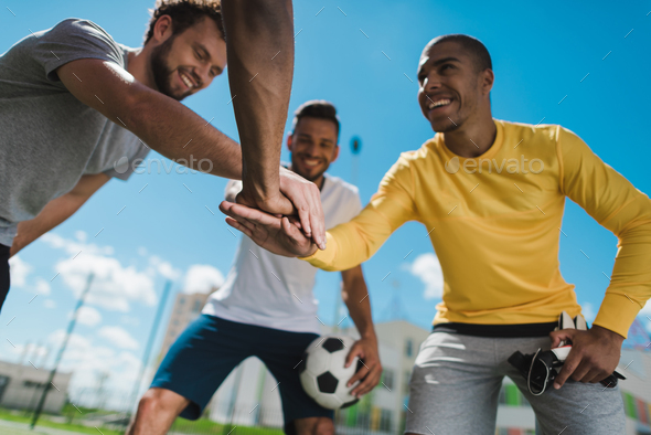 Low angle view of happy multiethnic soccer team holding hands together before game - Stock Photo - Images
