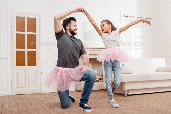 multicultural father and daughter in pink tutu tulle skirts dancing at home - Stock Photo - Images