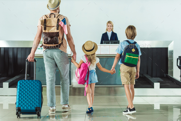 back view of family with backpacks going to check in desk at airport - Stock Photo - Images