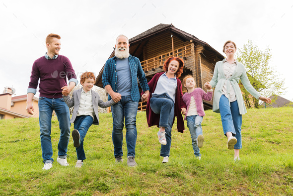 happy family holding hands together while running near country house in village - Stock Photo - Images
