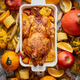 Thanksgiving dinner table with roasted whole chicken or turkey, pumpkin, baked potatoes, chestnuts - PhotoDune Item for Sale