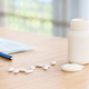pills with white plastic medicine bottle on the table - PhotoDune Item for Sale