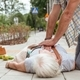 Man performs a heart massage on an senior lady who fainted on the street - PhotoDune Item for Sale