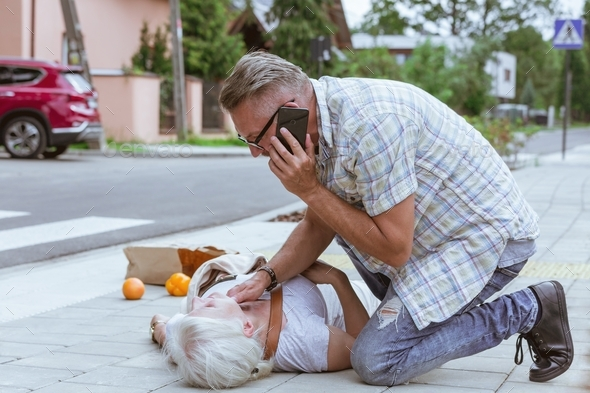 Senior passerby kneels beside the person who fainted on the street and calls an ambulance - Stock Photo - Images