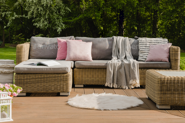 White rug on wooden terrace in stylish garden with wicker furniture with pillows - Stock Photo - Images
