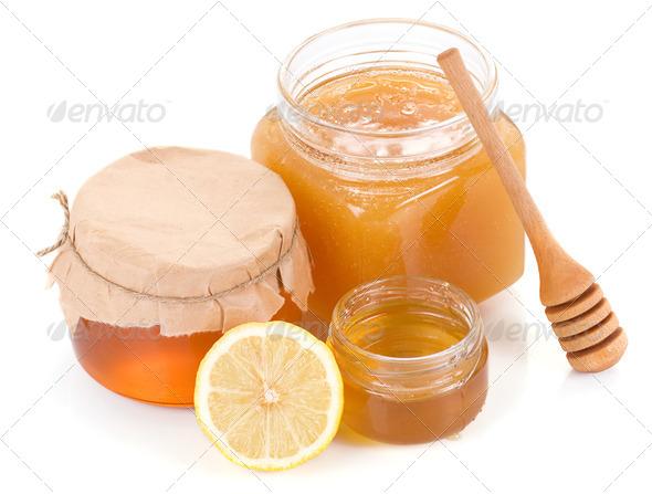 pot full of honey and lemon isolated on white - Stock Photo - Images