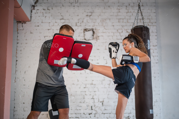 Training of a professional female fighter. The girl works out a kick on the paw, which is held by her individual trainer.