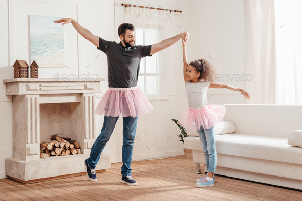 multicultural Father and daughter in pink tutu tulle skirts dancing together at home - Stock Photo - Images