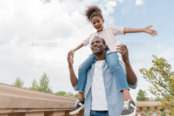 low angle view of smiling african american father and daughter piggybacking together in park - Stock Photo - Images