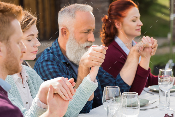 family holding hands while praying during dinner at countryside - Stock Photo - Images