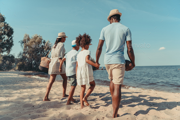 back view of african american family holding hands and walking on beach - Stock Photo - Images