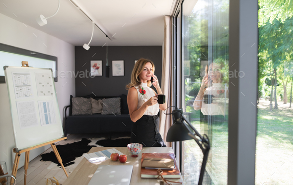 Mature woman working indoors in home office in container house in backyard - Stock Photo - Images