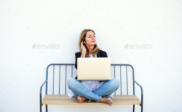 Mature woman working in home office outdoors on bench, using laptop - Stock Photo - Images