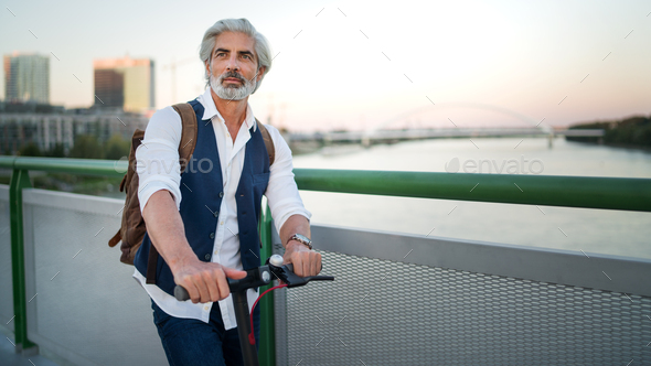 Mature man commuter with electric scooter outdoors in city, going to work. Copy space - Stock Photo - Images