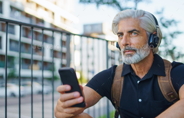 Portrait of mature man with headphones sitting outdoors in city, using smartphone - Stock Photo - Images